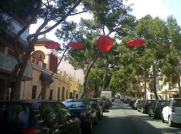 Foto de paraguas rojos en un pueblo de España enviada a Antonia J. Corrales por Virginia Vivó Verdejo